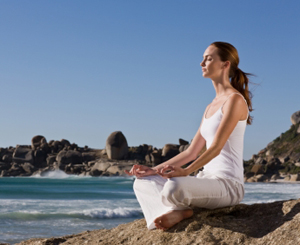 Beautiful young lady meditating on rock by sea