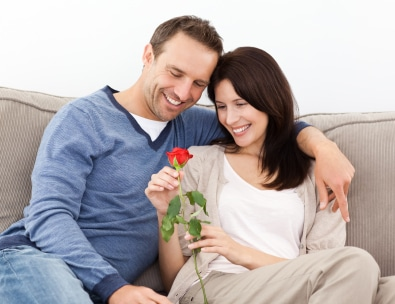 Portrait of a lovely couple looking at a red rose sitting on the sofa